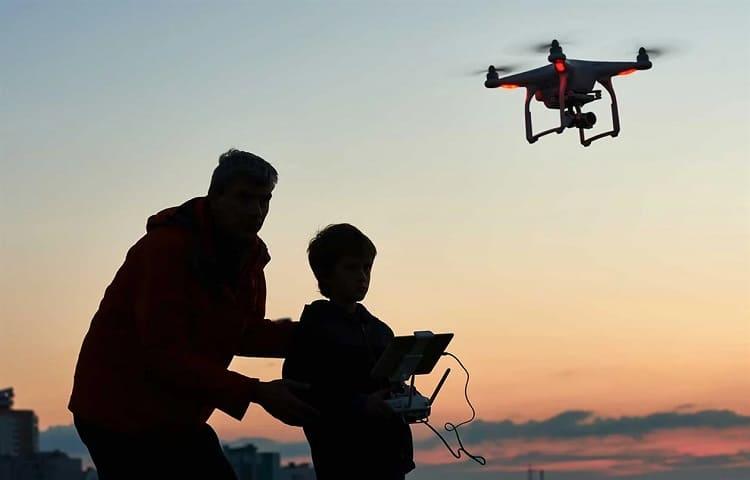 boy flying camera drone with dad